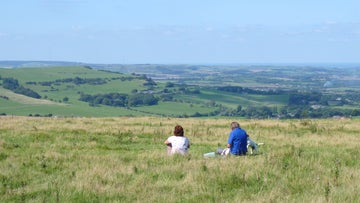 Two dog walkers sit on the grass on Ventnor Downs and take in the wide views