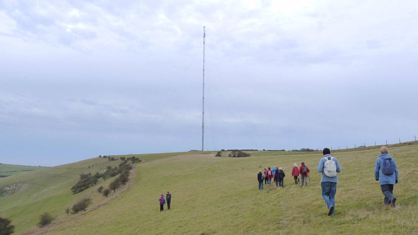 Walkers head along the ridge of Chillerton Down towards the transmitter mast