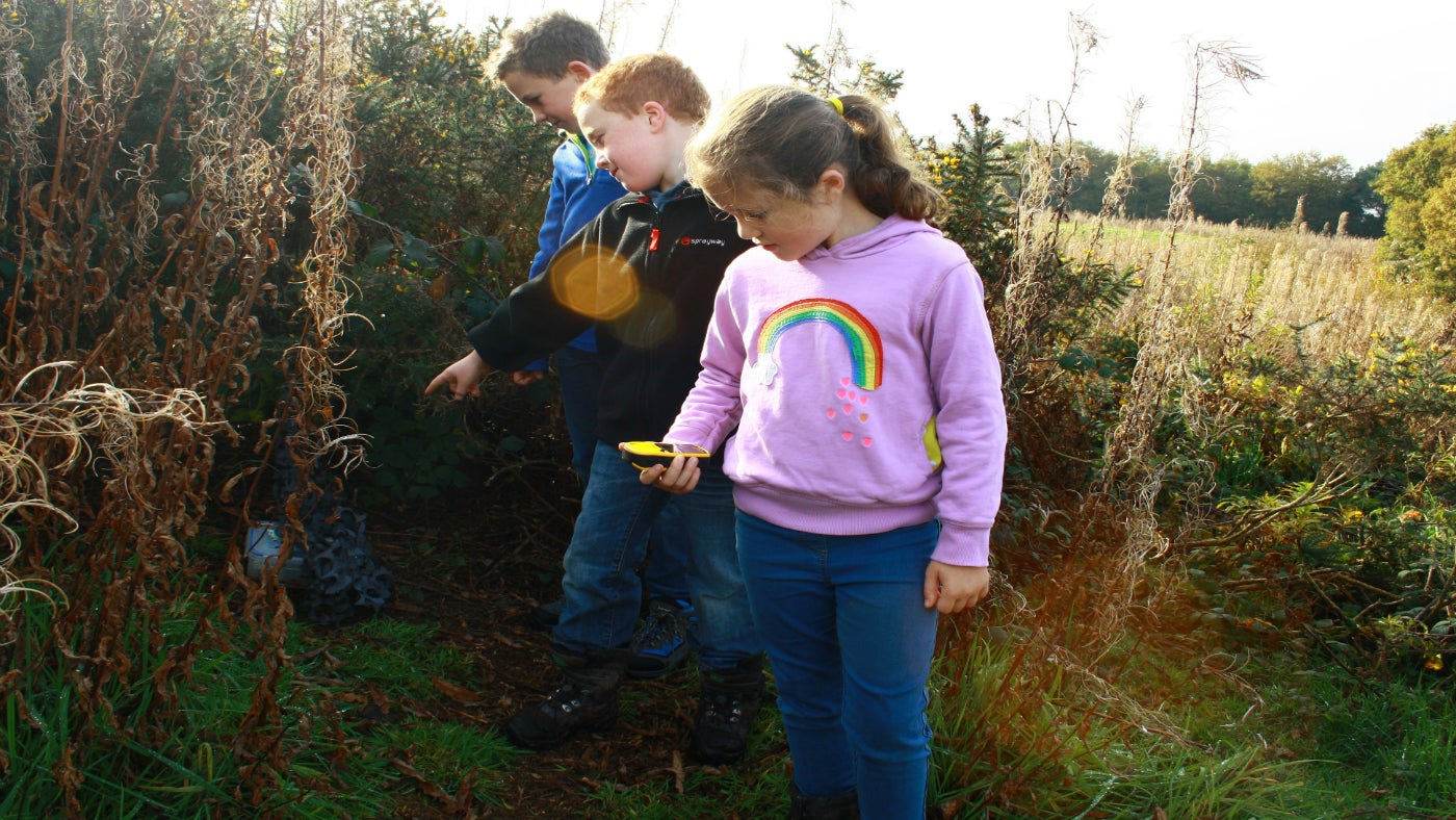 three children in countryside using a gps unit to hunt for a geocache