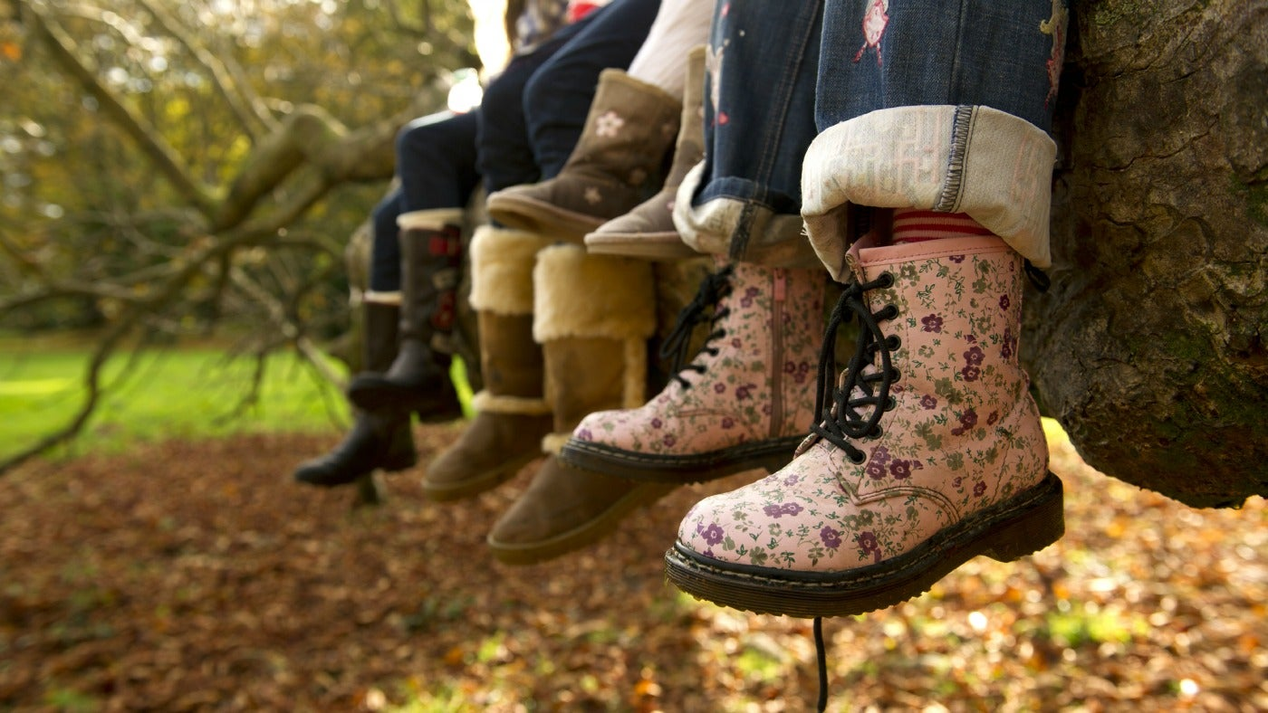 Children with wellies on sitting on a tree