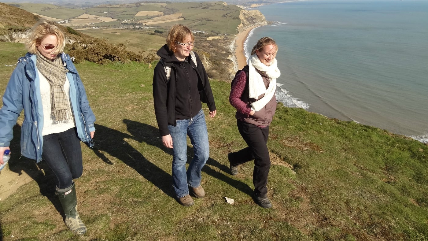 Three female walkers on the top of Golden Cap on a cold, sunny day