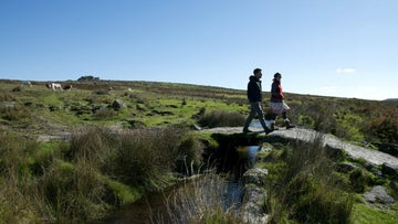 Walkers crossing a leat on Trowlesworthy Warren, near Cadover Bridge, Upper Plym Valley