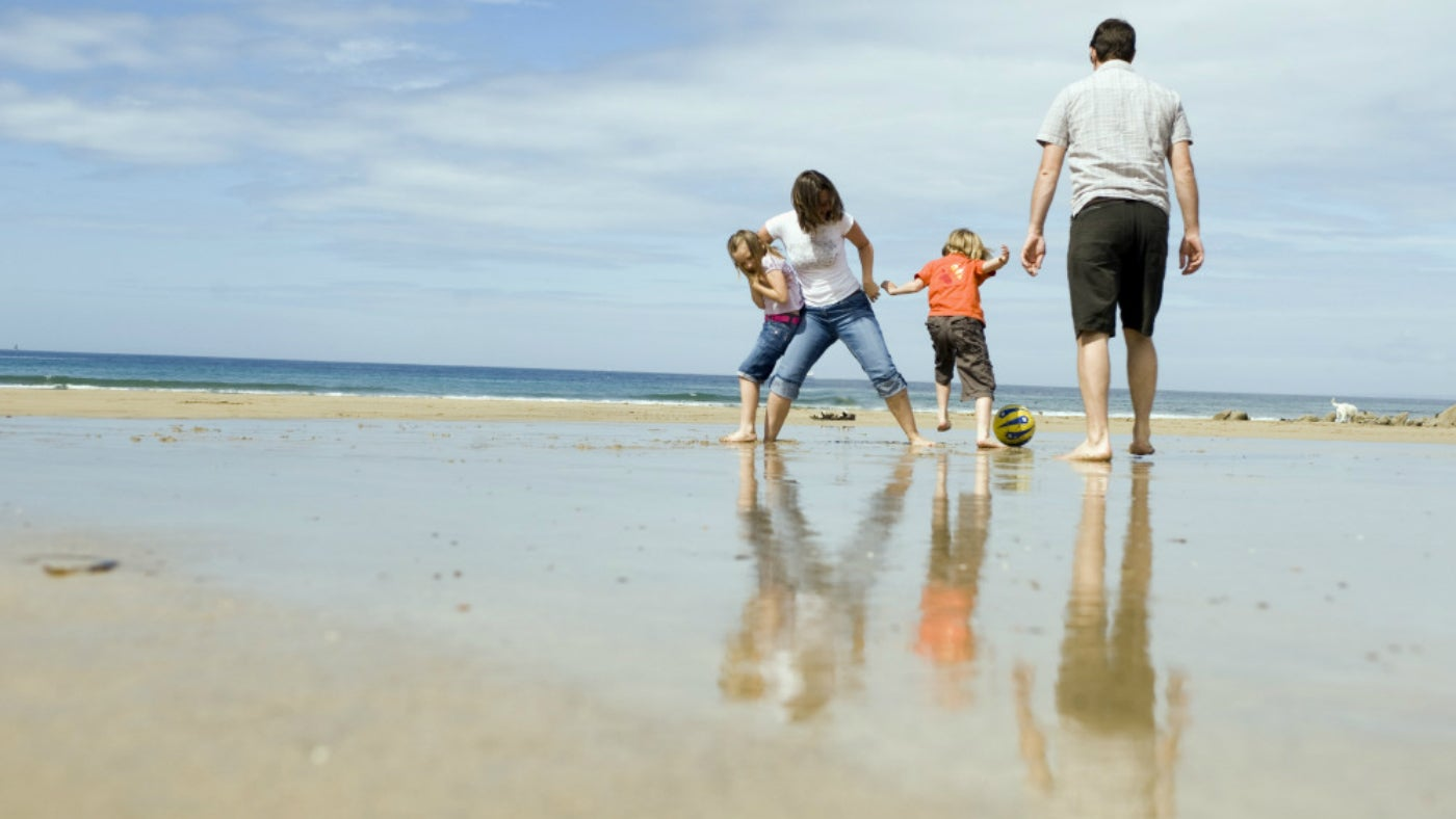 A family enjoy the beach at Poldhu