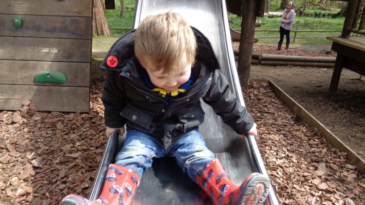 A young visitor enjoys one of the outdoor adventure playground's new slides