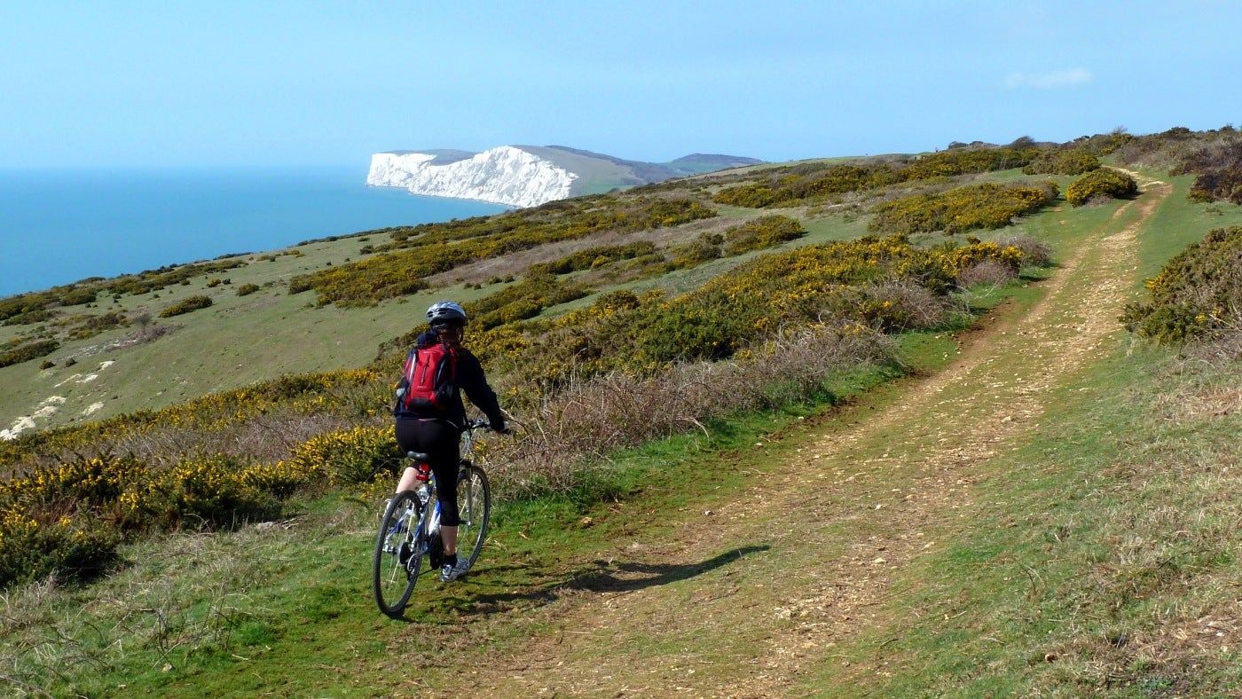A cyclist on Compton Down, heading for Freshwater Bay seen in the distance