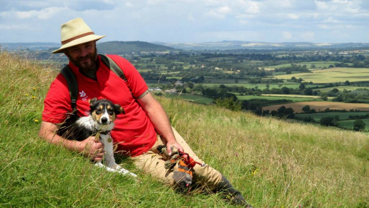 Ranger Clive Whitbourn resting on the grassy slope of Hambledon Hill with Rosie the collie dog