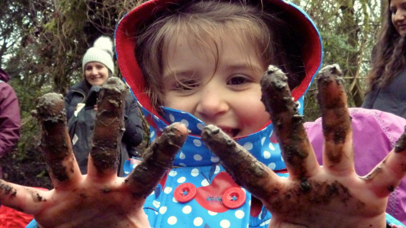 Child gets muddy hands at Box Hill toddler group