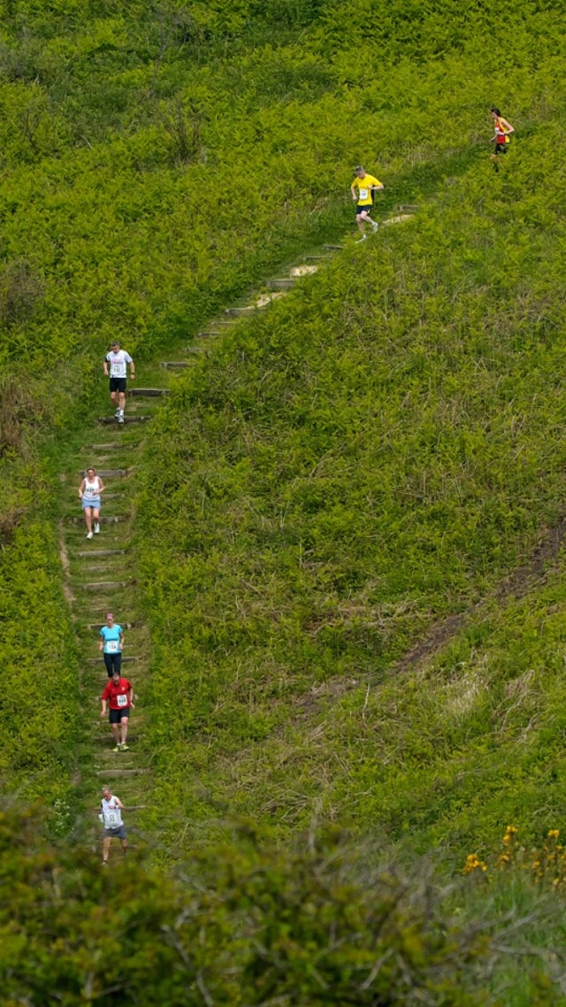 Runners tackle steps down a steep cliff side