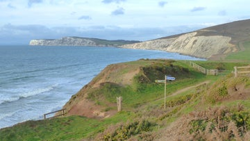 The footpath sign ahead beckons to the chalk cliffs of Freshwater Bay