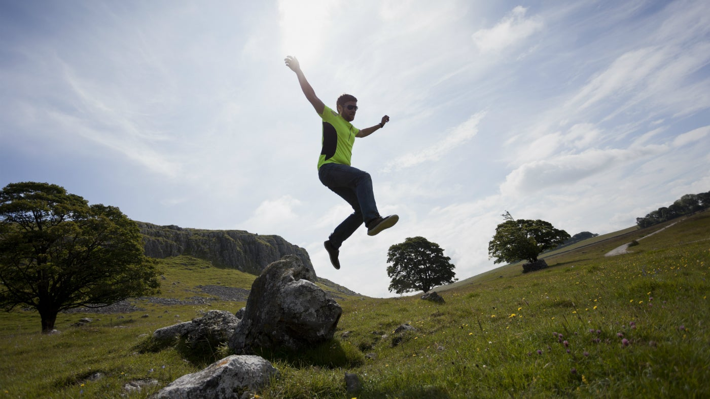 Runner jumping off a rock at Malham Tarn