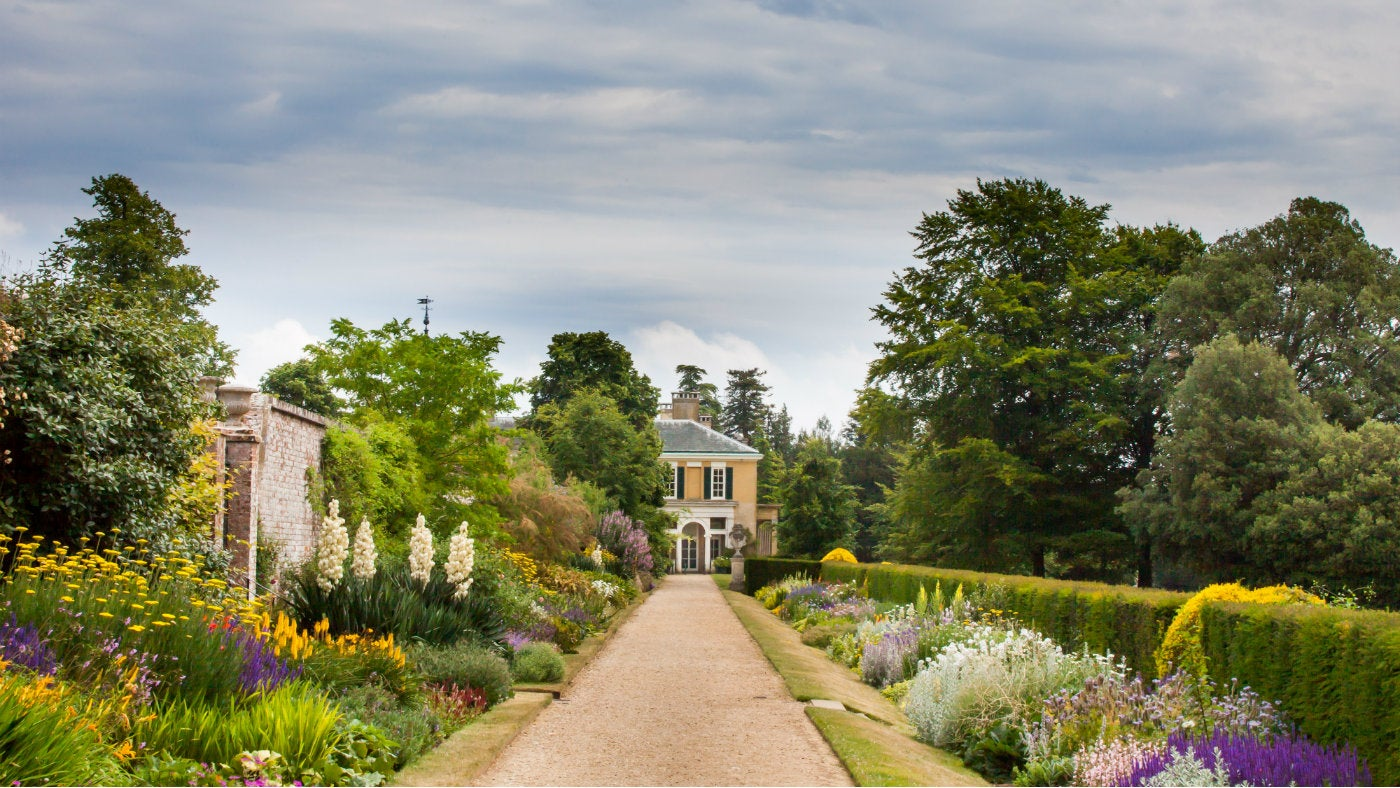 A view of the blooming herbaceous borders at Polesden Lacey looking onto the corner of the house.
