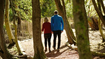A couple walk through sunlit woods