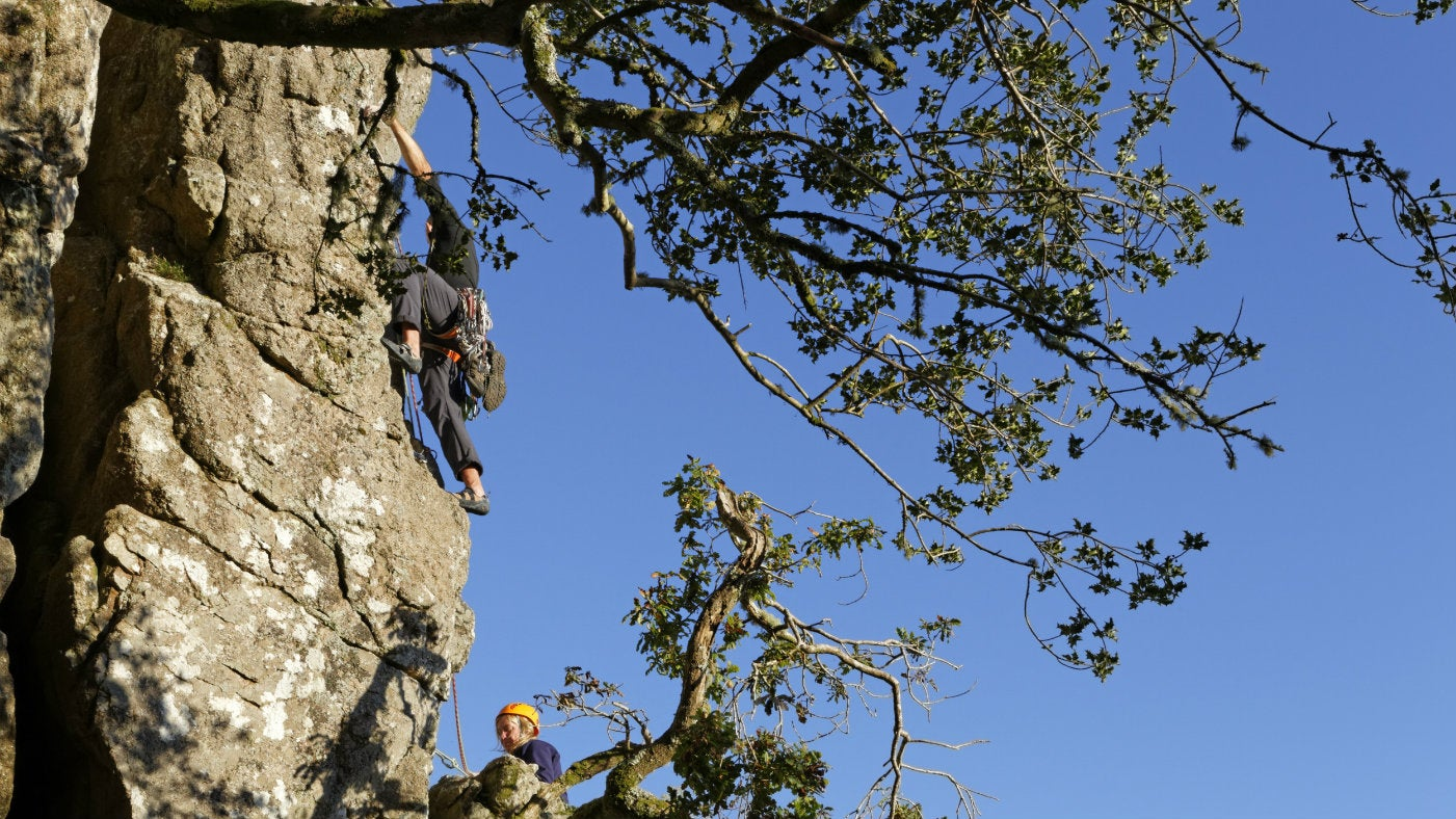 People climbing and abseiling on rocks at Dewerstone Wood, in the Upper Plym Valley, Dartmoor National Park, Devon