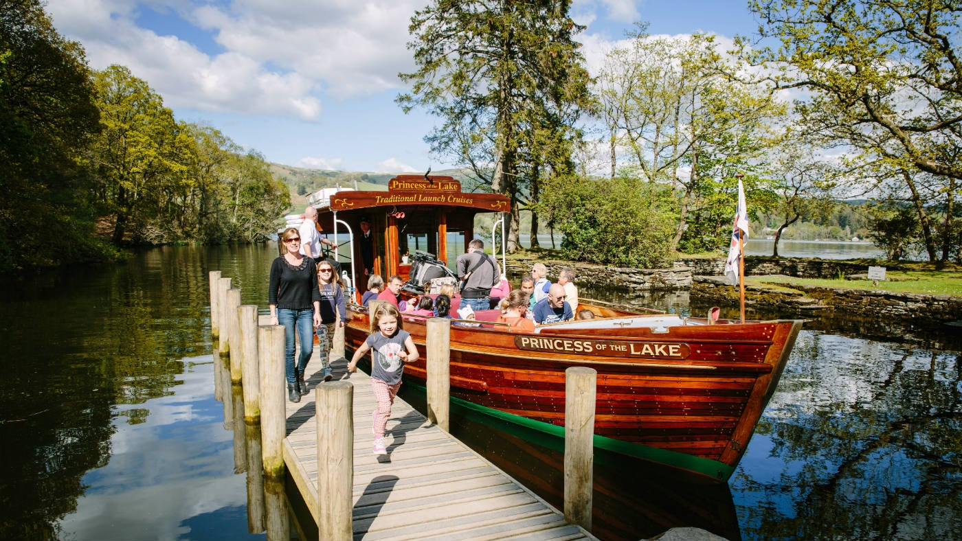 People arrive at Wray Castle by boat