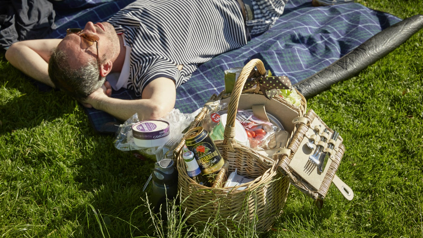 Man lying on a rug with a picnic