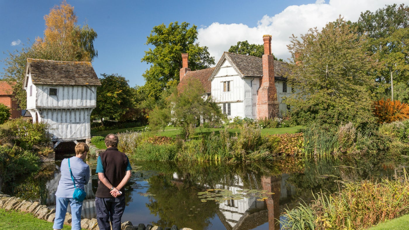 Brockhampton manor house and moat with two visitors in front of moat and tall trees behind