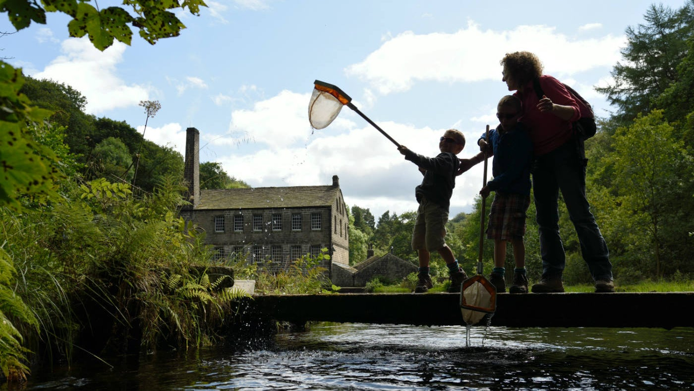 A family enjoying pond dipping in the mill pond in front at Gibson Mill, Hardcastle Crags