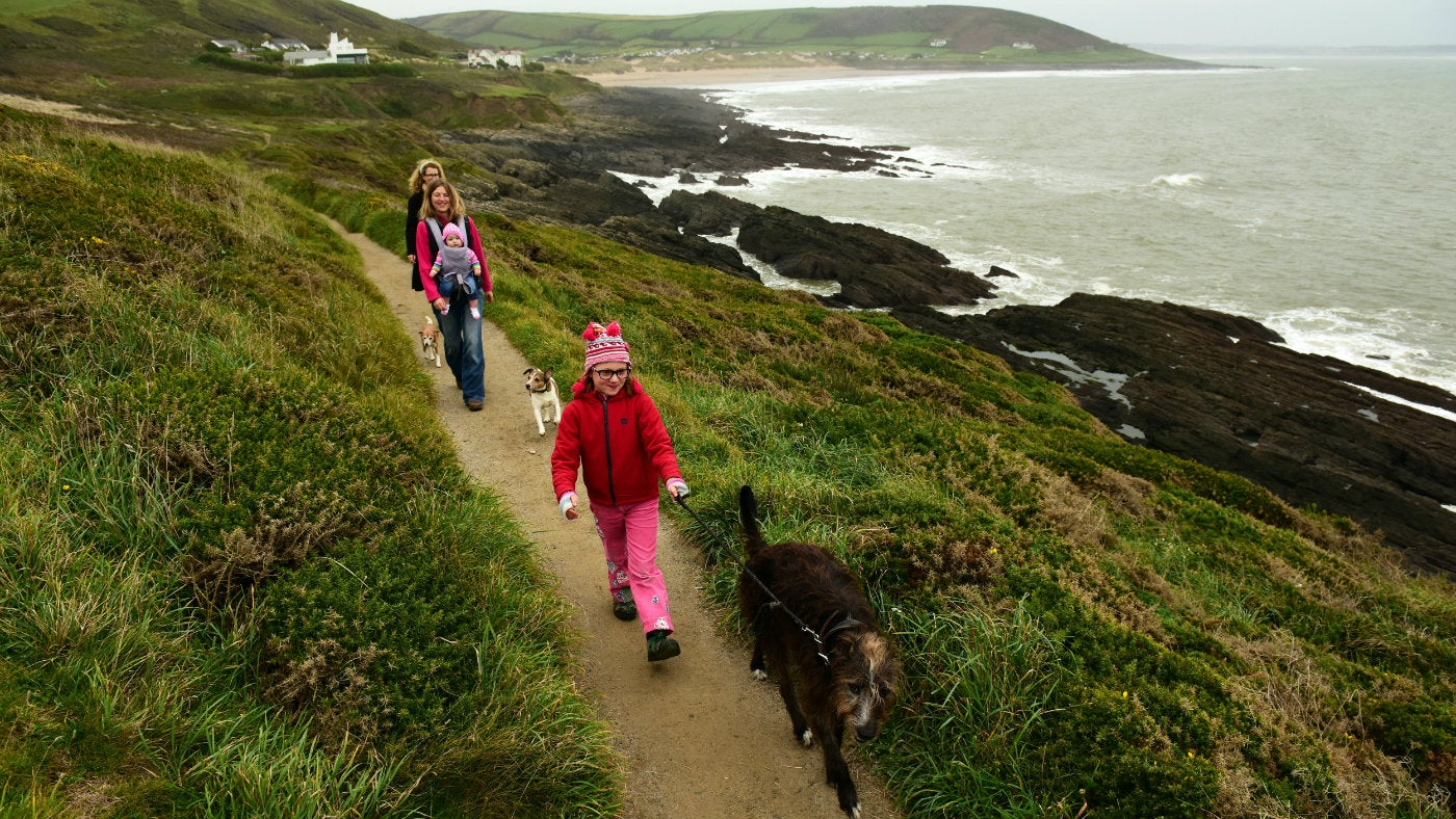 People walking along the coast path with the sea behind them