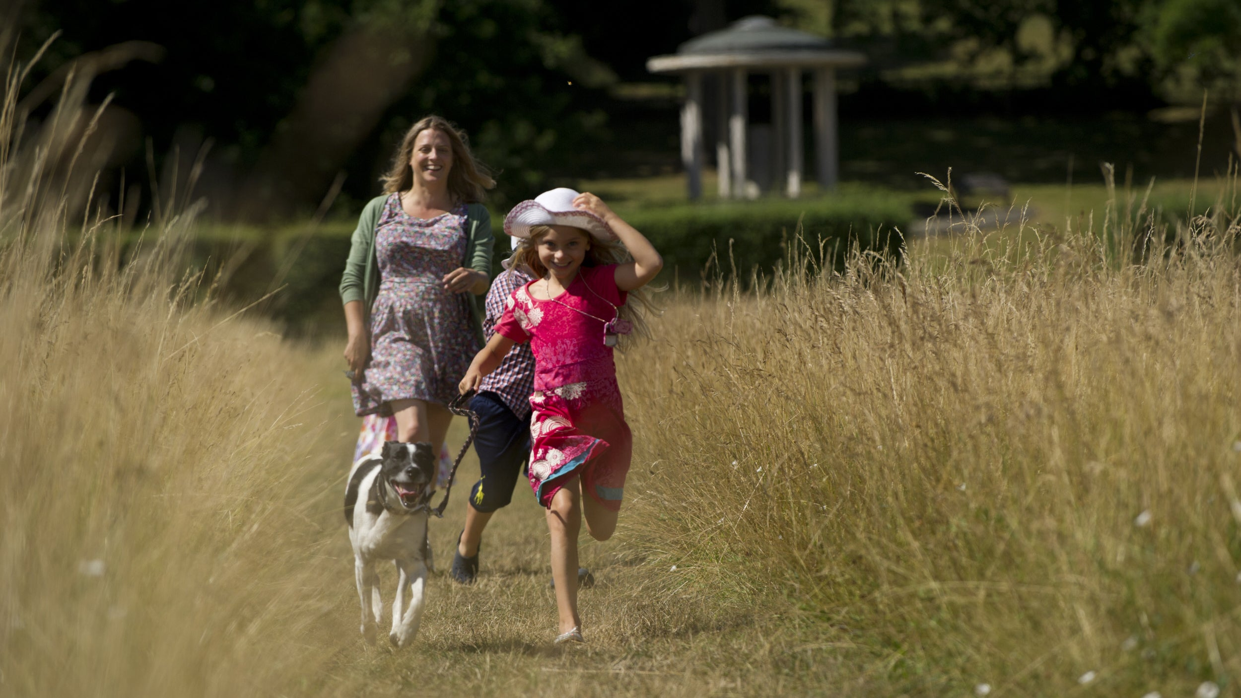 A family walking the dog by the Magna Carta Memorial at Runnymede