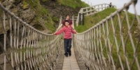 Picture shows children crossing the bridge at Carrick-a-Rede