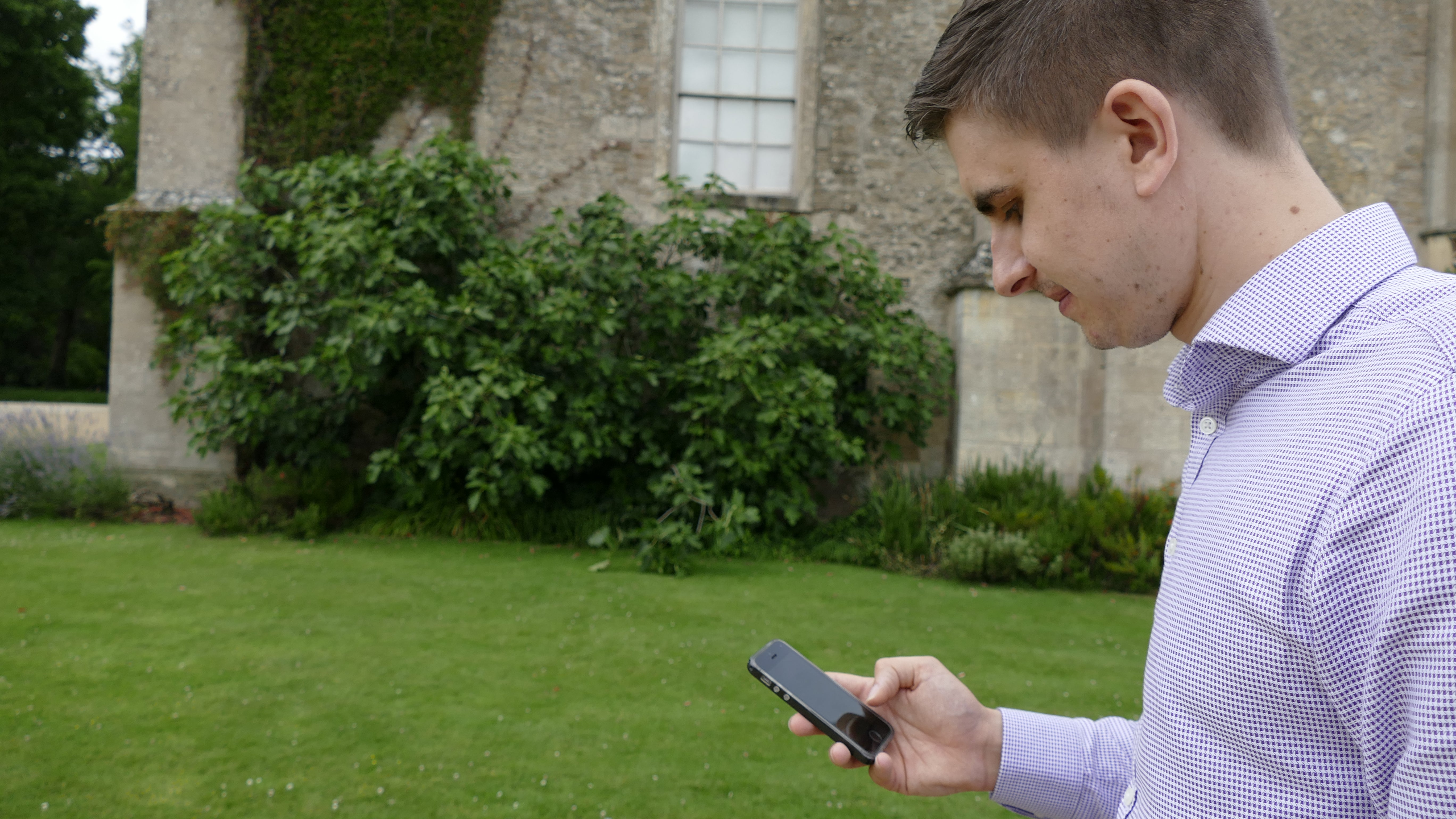 A man playing on his phone at Lacock Abbey in Wiltshire