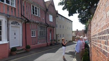 Visitors on a group tour of the village with the Lavenham Guildhall, Suffolk