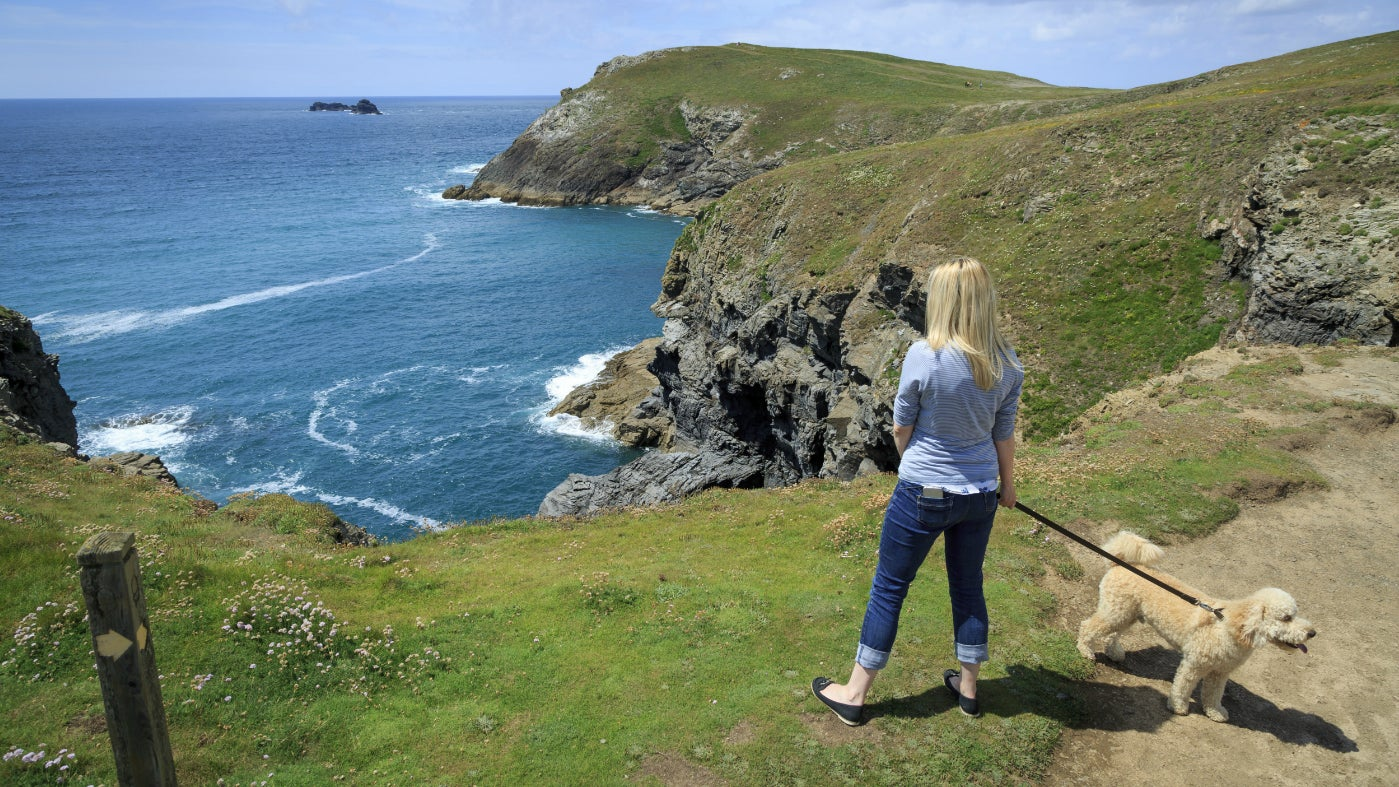 A walker with her dog at Trevose Head, Cornwall