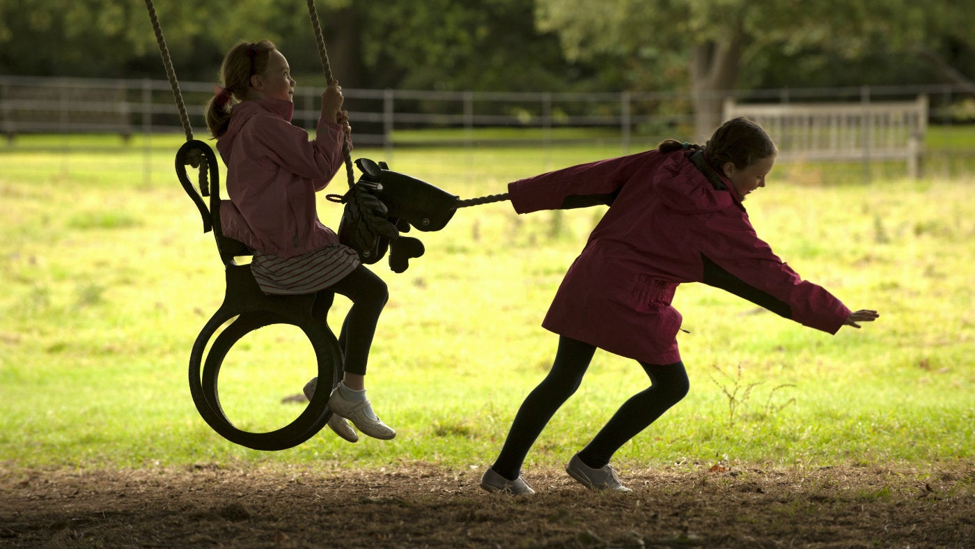 Children playing on a swing