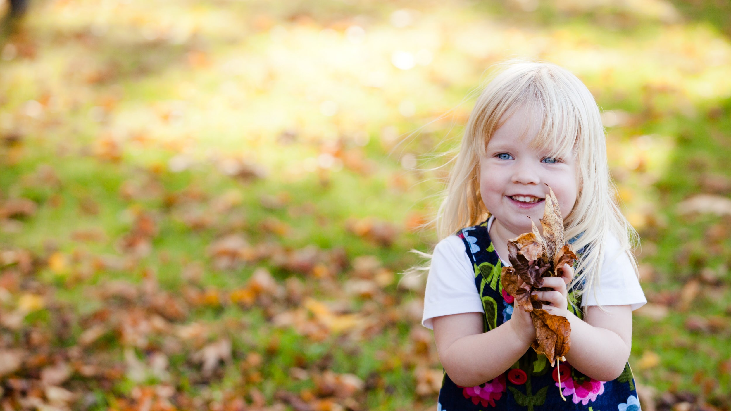Young girl playing with fallen leaves.