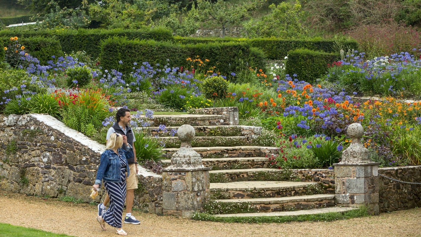 Two visitors walking by the steps and flower borders in the gardens at Mottistone on the Isle of Wight