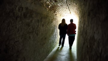Two people walking down a tunnel in Bembridge Fort on the Isle of Wight