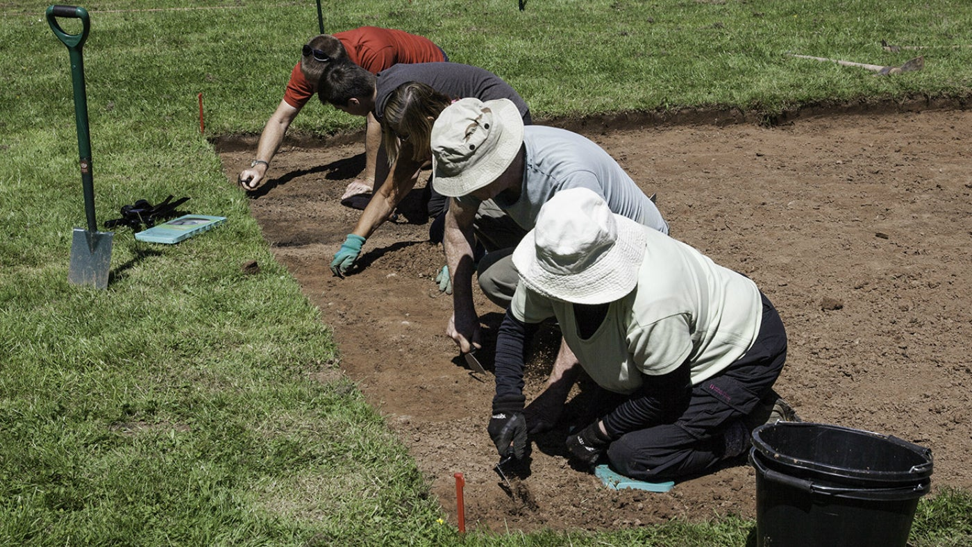 three volunteers excavating with trowels in a trench
