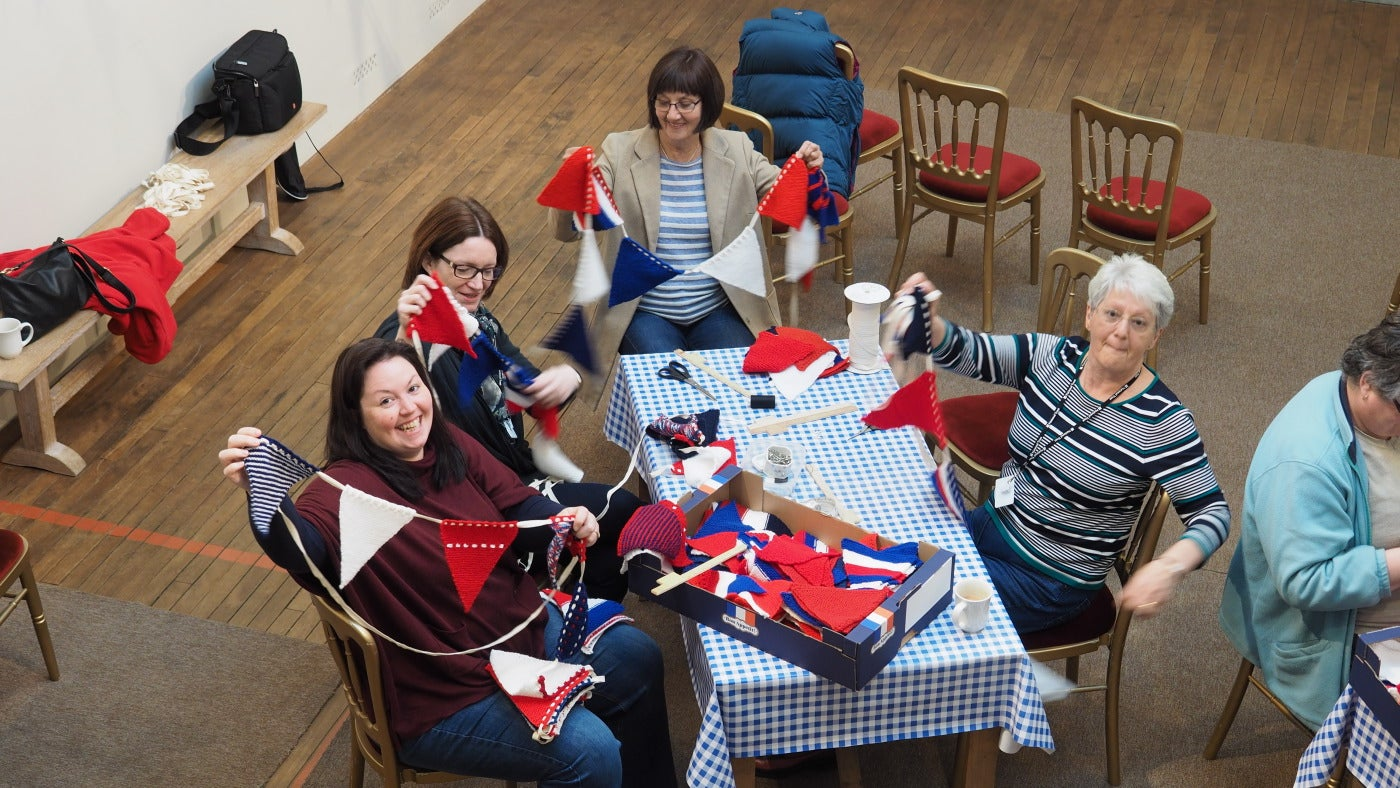Groups of people holding up knitted bunting