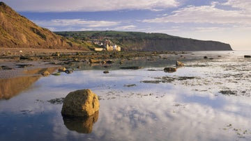 Reflections of clouds in water on the beach at Boggle Hole looking towards Robin Hood's Bay
