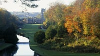 a stunning autumn view through the trees looking down on the abbey ruins of fountains abbey