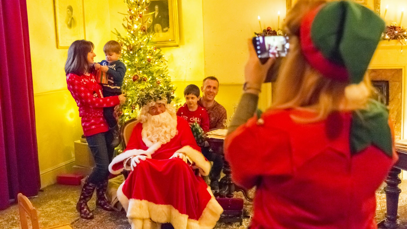 An elf photogprahs Father Christmas and visitors to his study at Attingham Park