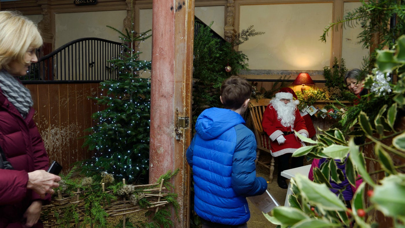 A boy and his Grandmother greaat Father Christmas in a stable