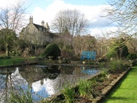 View of the house at The Courts Garden across the lily pond in February