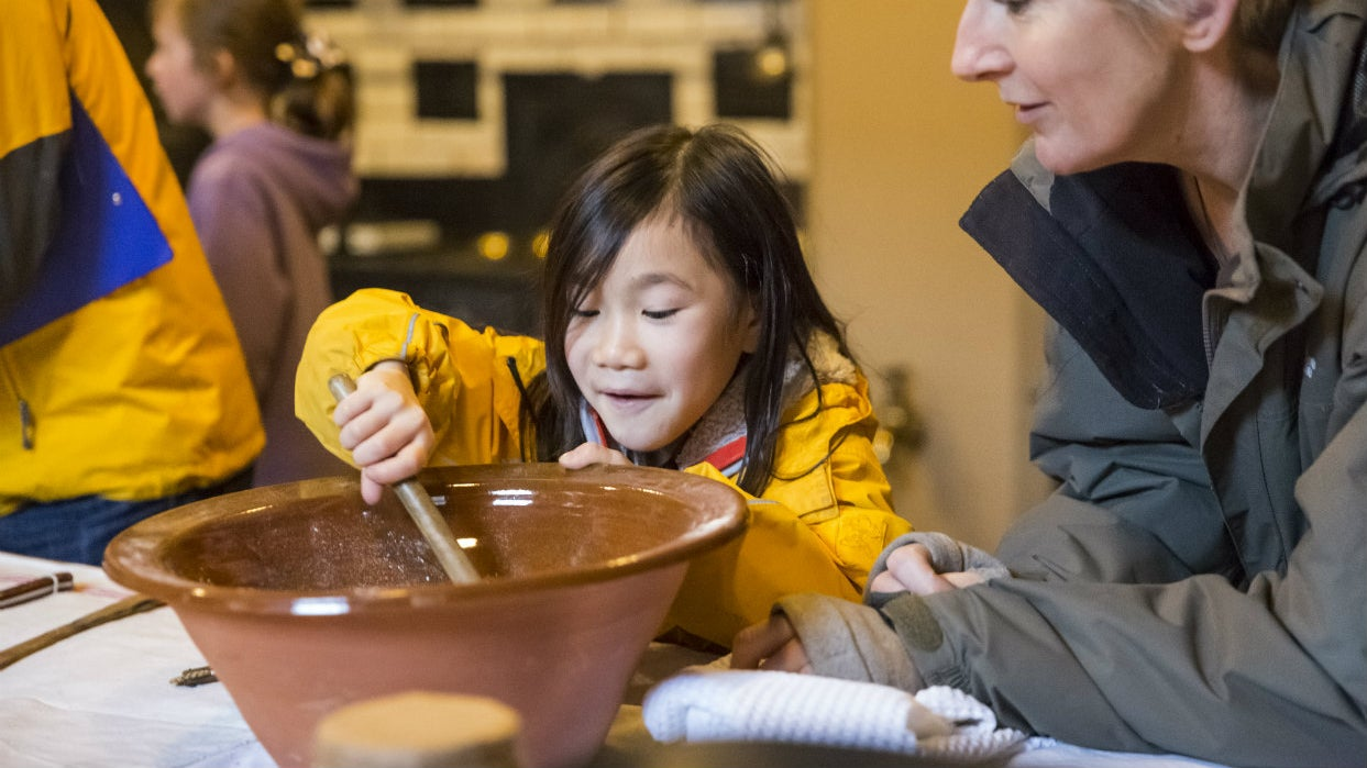 Young girl and woman mixing cake mixture in a large mixing bowl