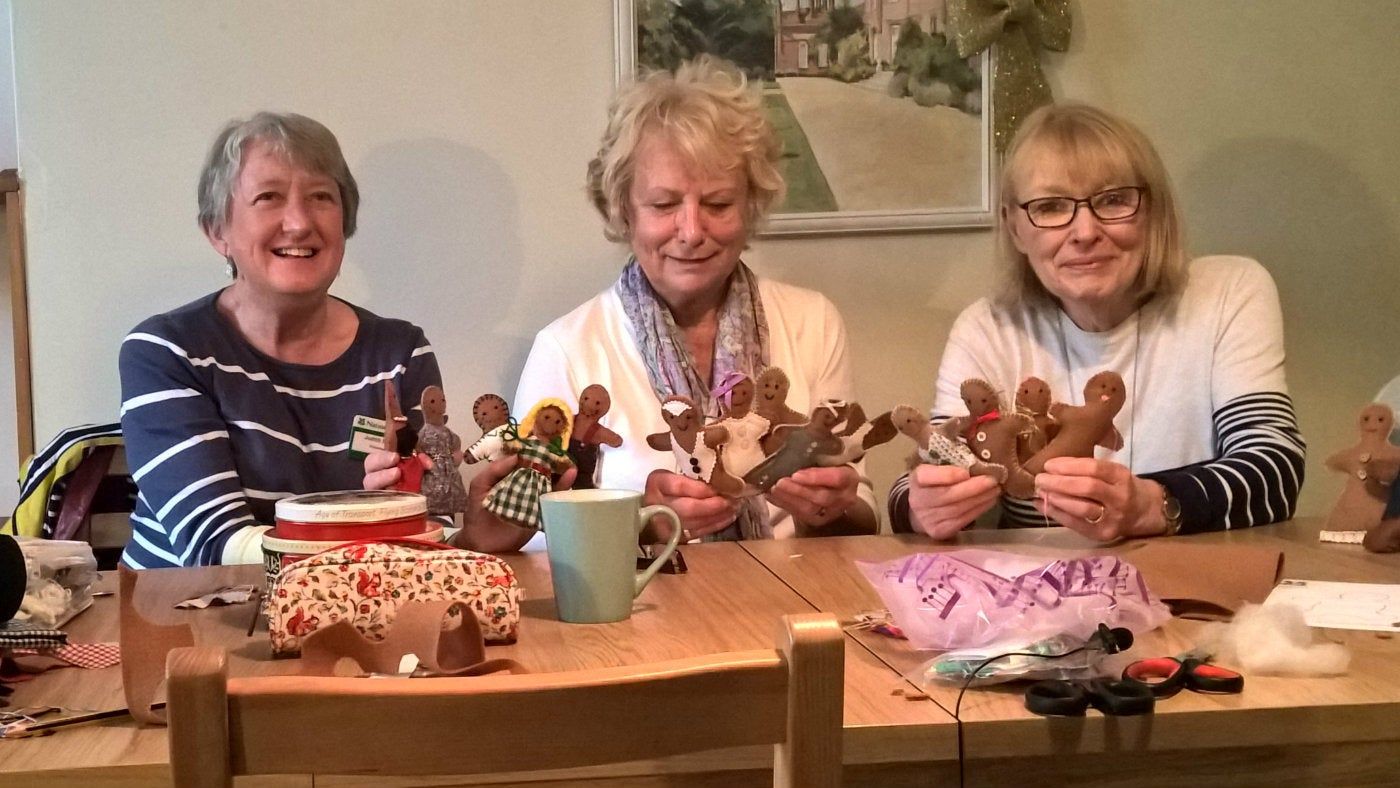 Three volunteers sat at a craft table making gingerbread people