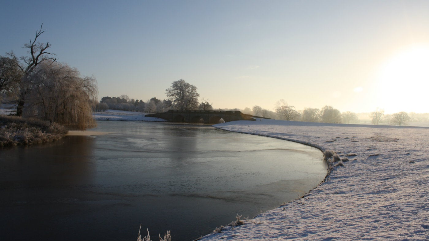 a lovley winter day at kedleston hall looking towards adam bridge over the frozen lake