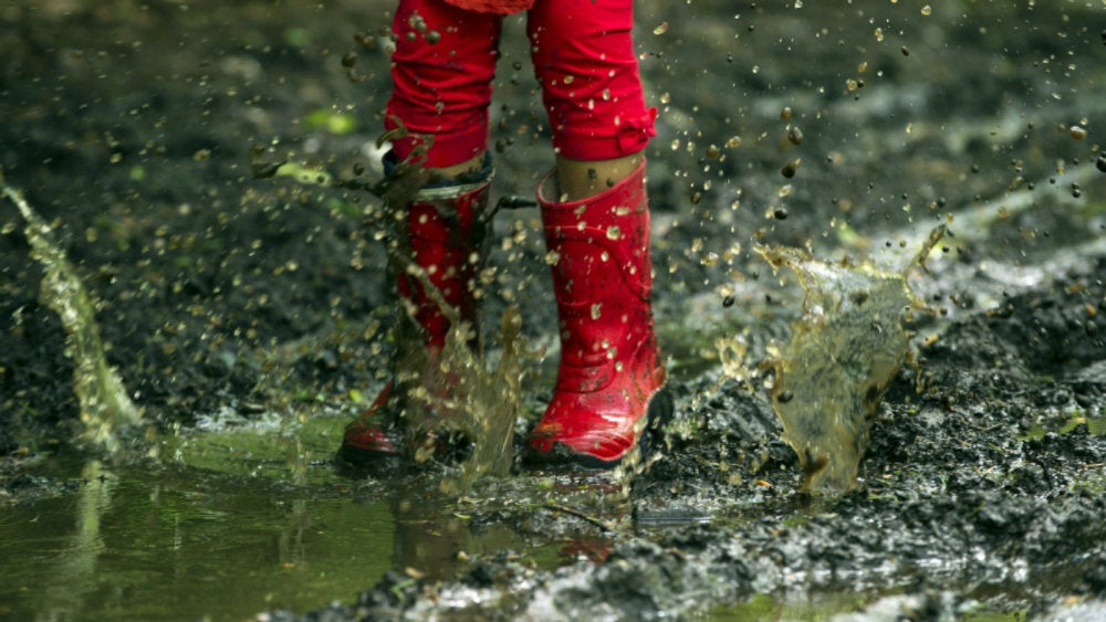 some red wellies jumping in a puddle