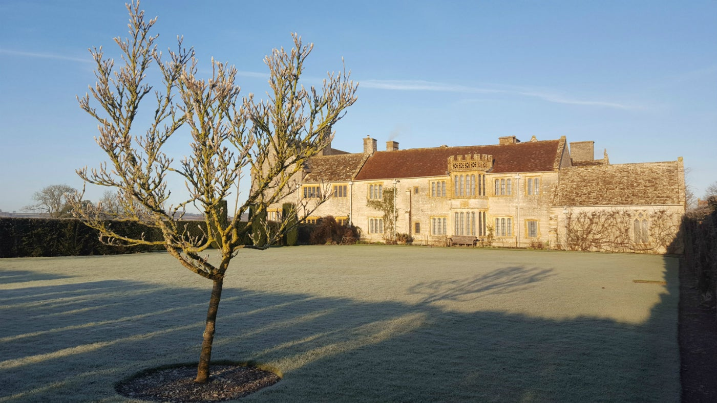 Lytes Cary Manor garden showing croquet lawn and house in winter with frost