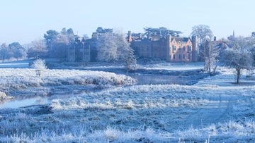 Charlecote house view across river on frosty day in winter