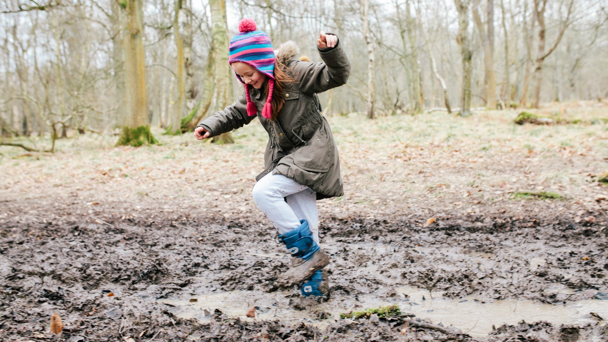Girl stomping in mud in woodland on winter's day