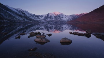 Llyn Ogwen, still waters, with the snow-capped peak of Y Garn, Snowdonia, Wales