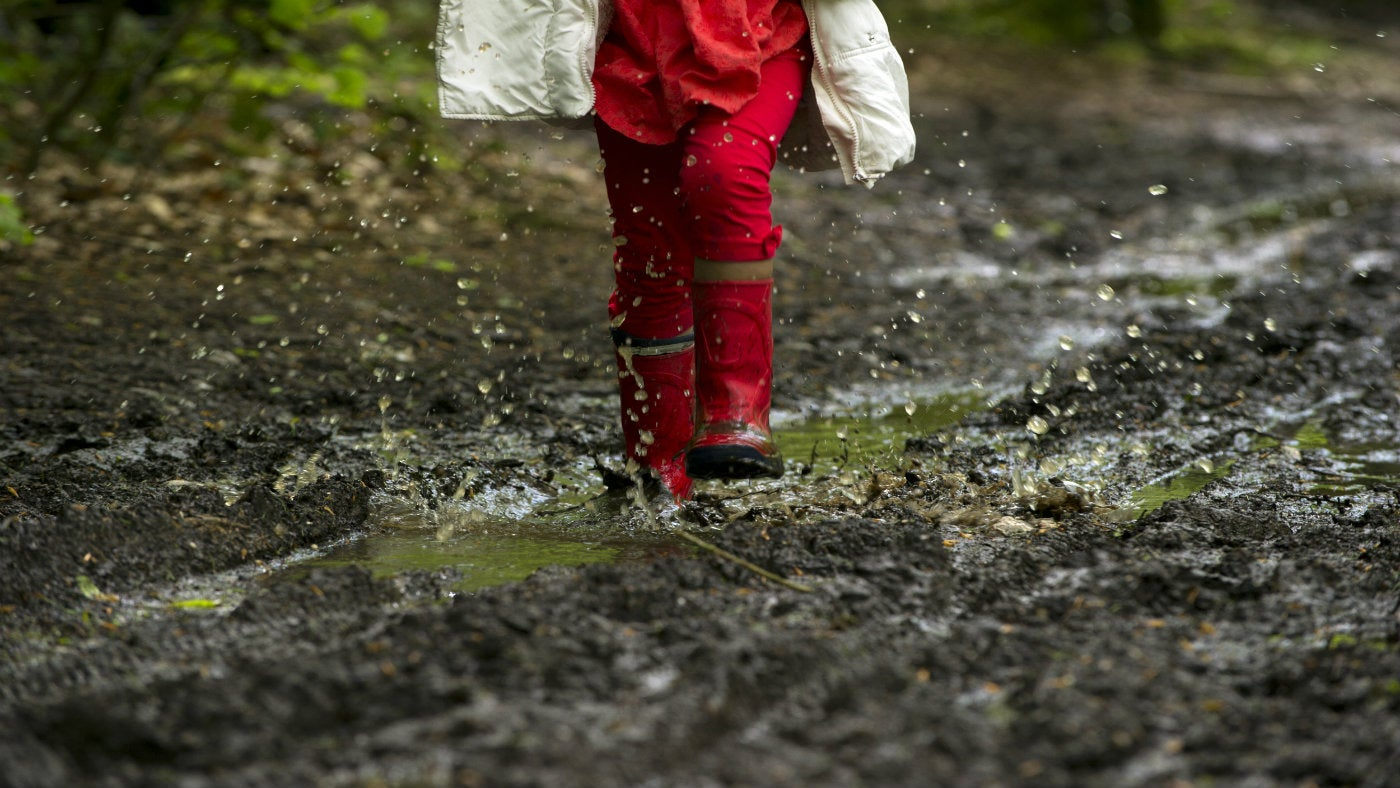 A child jumping in a muddy puddle