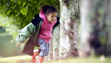 Little girl running in the grounds of a National Trust property
