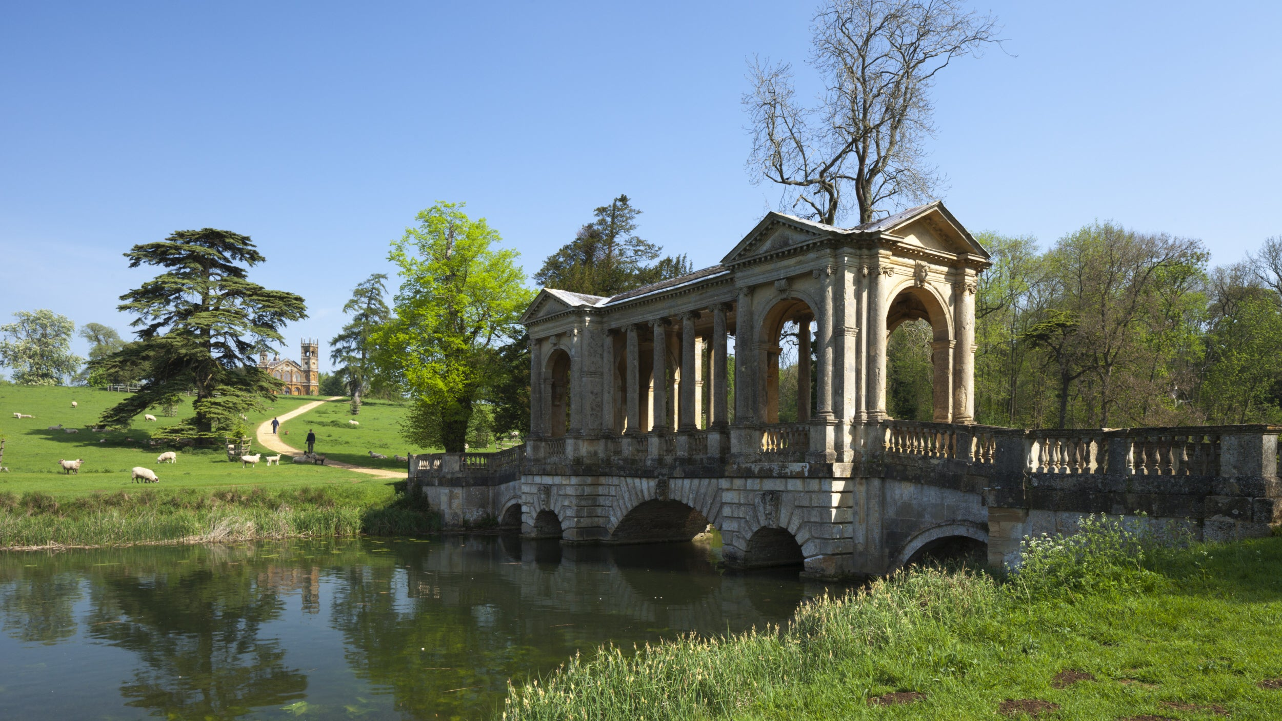 A fine roofed stone bridge over the lake in spring