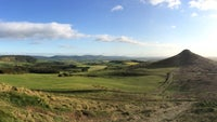 A panoramic view of Roseberry Topping under blue skies taken from Little Roseberry.